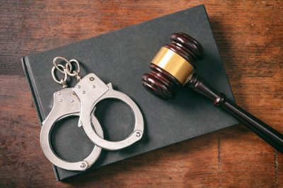 Handcuffs, gavel on book on a wooden background.