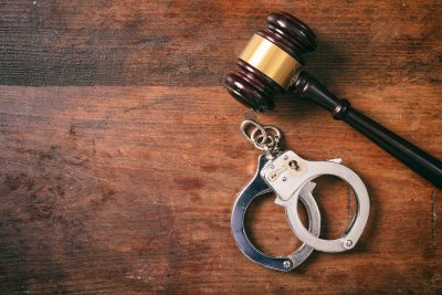 Handcuffs isolated and a gavel with copy space on a wooden background.