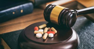 Judge gavel and drugs on a wooden desk